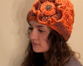 handmade orange flowered hat with a beautiful gold pendant.