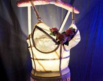 A Hand Made Tramp Lamp crafted from a vintage cream long line bra trimmed in pink beads at the bottom and silk pink flowers at the bust