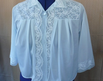"""Light Blue, Nylon Bed Jacket, Size Medium.  A vintage, """"Henson Rickernick"""" brand.  It has white lace inserts and self covered buttons"""