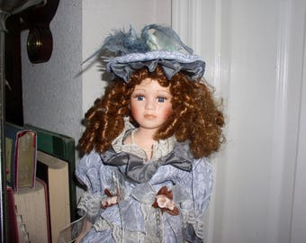 pretty haunted porcelain doll Zasya in cool blue Victorian clothing loves business stays cool