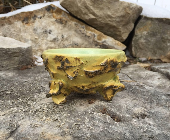 small ceramic bowl in pale orange, golden yellow, and navy blue