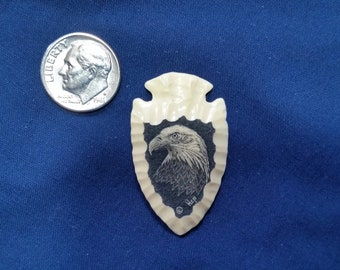"Eagle Scrimshaw on Small Arrowhead By: Hop, Reproduction Polymer Scrimshaw. 1 /12"" tall by 7/8"" wide."