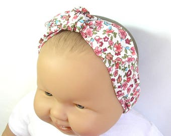 Baby headband made of white cotton fabric with flowers with elastic at the back