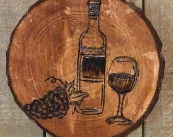 Wood burning art of wine bottle, wine glass and grapes