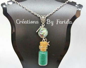Necklace with a vial pendant filled with green beads blue under a blue oval bead