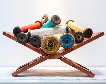 Rustic antique wooden bobbin with woollen thread