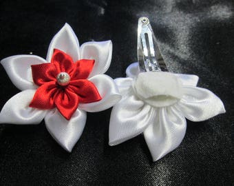 Adorned with a red and white satin flower with a hair clip is adorned with a silver bead