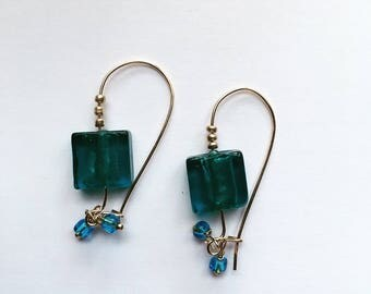 Earrings in gold and blue glass beads