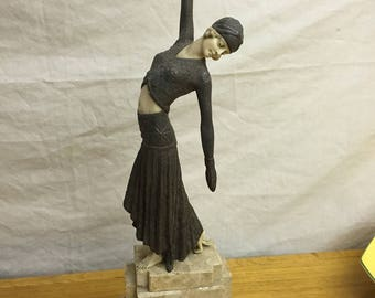 An Art Deco style figurine of a lady wearing a pleated skirt