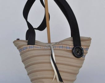 Bag shaped caramel colored gift-wrapped, through tartan, black handles.