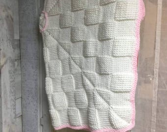 Knitted pink and white baby blanket