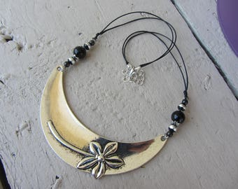Necklace with large bright silver tone metal bib and volume flower, glass beads and black waxed cotton cord