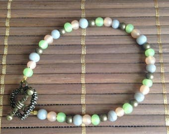 Bronze bracelet with green, orange and gray glass beads