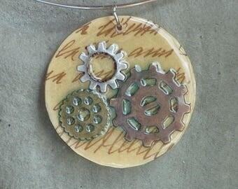 Pendentif rond, rouages de montre, vieille écriture