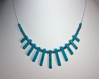 Necklace gemstone beads of turquoise howlite adorned with silver metal beads.