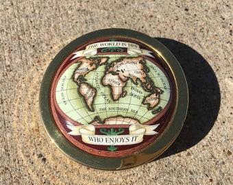 Halcyon Days brass and enamel paperweight 'The World Is His Who Enjoys It'