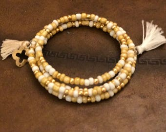 Wrap bracelet, gold and white colored beads with tassels and gold charm