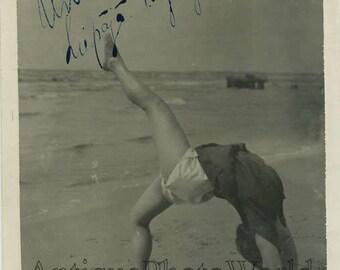 Woman gymnast posing on beach