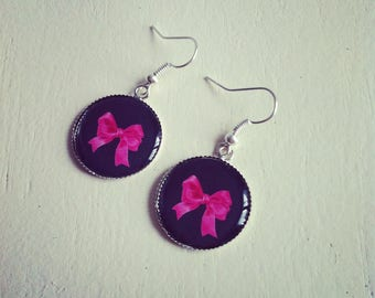 Silver earrings cabochons bows pink on black background