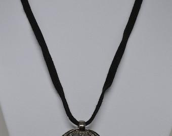 Lovely Silver tone metal pendant on black string