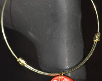 Gold bangle bracelet with red clay charm