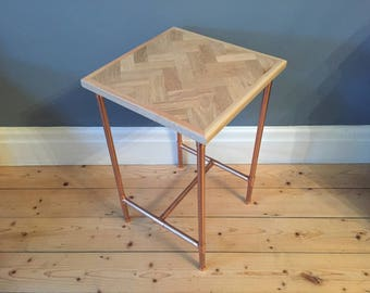 Side table in a retro industrial style with a copper pipe frame and reclaimed oak herringbone/parquet style top