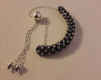 Bracelet 925 sterling silver Figaro chain 1-1 with a ball slider clasp there is a myuki hand made bead in the centre in black and silver