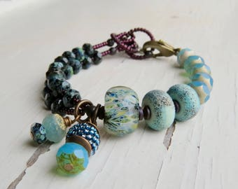 In the Depths - handmade artisan bead bracelet with artisan lampwork, handwoven and pressed glass in black and turquoise - Songbead, UK