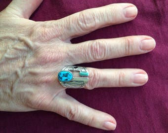 Man's silver and turquoise ring, Navajo made, sterling silver band, adjustable, with incised carving in geometric pattern. D: 2cm