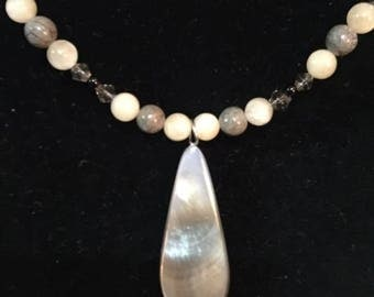 A grayish brown shell pendant with calcite, pink leopard jasper, black agate and grey faceted bi-cone beads.