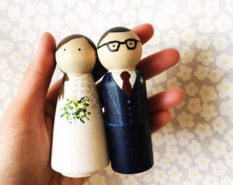 Hand painted wooden wedding cake toppers. Personalised to look like the happy couple! These can also be a unique wedding gift