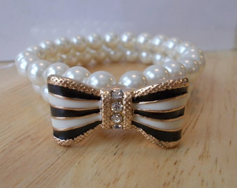 2 Row White Sea Shell Pearl Stretch Cuff Bracelet with a Black, White and Clear Rhinestone Bow