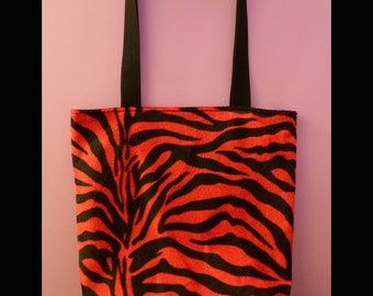 Red furry zebra-print tote bag with flat bottom and inside zip