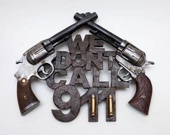 "Novelty Metal Wall Hanging: ""We Don't Call 911"" - Features 2 Six-Shooter Fake Guns on Top - 9-1/2"" x 11-1/2"""