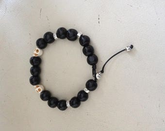 Trendy bracelet with black wooden beads, Tibetan silver beads and two howlite skulls