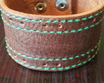 Beautiful brown leather with lovely green stitching.