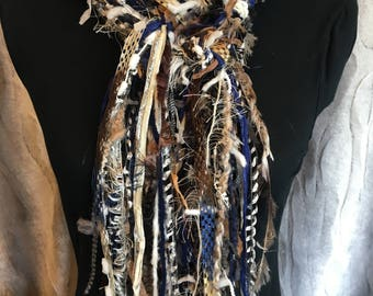 Unique fashion scarf in shades of blue, taupe, black, brown, cream and white.