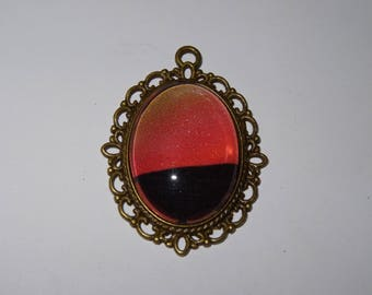 Bronze metal pendant antique red orange and black graphic