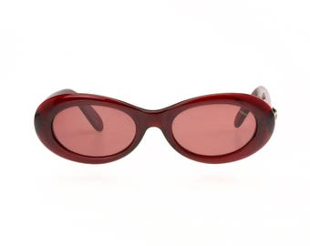 Vogart vintage sunglasses, bold oval shape, dark cherry-red shiny cello structure with coordinate lenses, cool metal logo on arms, 90s NOS
