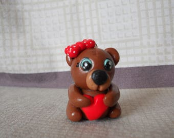 Brown Teddy bear with blue eyes, holding a red heart