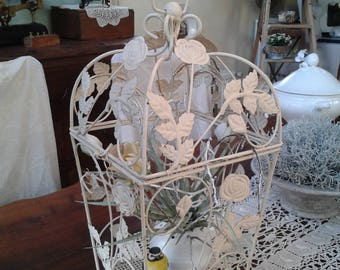 Shabby chic decor with its whistling bird in bird cage decorated with a flower pot and artificial flowers