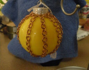 Glass christmas ornament with chainmail around it.