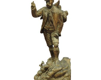 a large unfinished black forest poacher with ibex carving