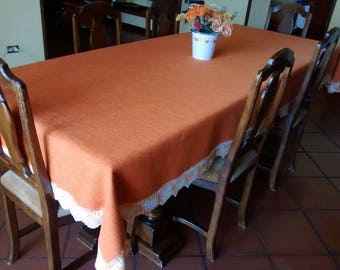 Table in orange heavy jute canvas, surrounded by crochet lace in orange shaded colour.