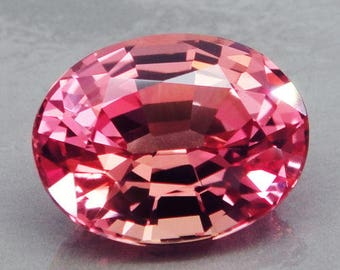 Pink sapphire, Padparadscha sapphire,  10.40 carats, 14.5 mm by 11.2 mm by 7.7 mm, oval brilliant faceted, synthetic corundum