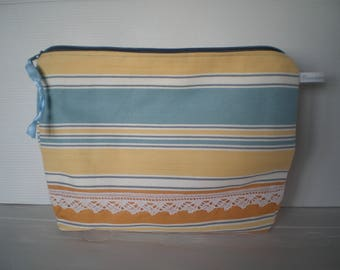 Blue and yellow striped toiletry lined white with yellow dots