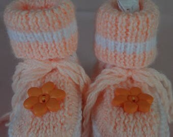 BOOTIES BABY ORANGE AND WHITE WITH FLOWER SHAPED BUTTON.