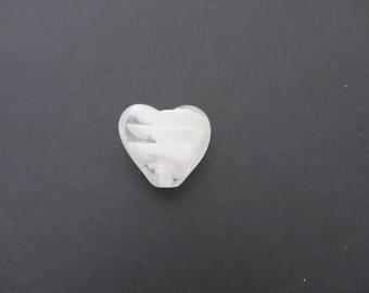 A heart-shaped white iridescent glass bead