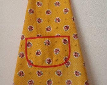Adult apron has bib fabric yellow flowers.