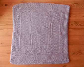 Pretty knitted blanket is hand crocheted